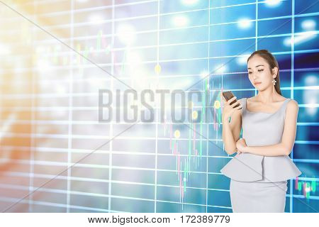 Businesswoman with trading online on smartphone with stock graphics on the background