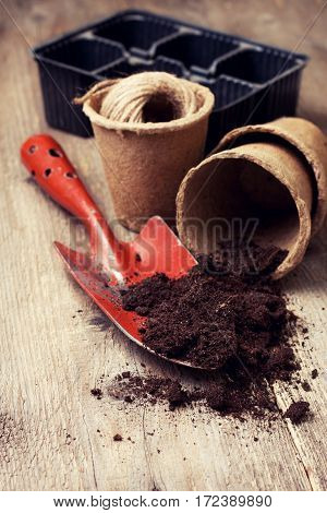 garden tools peat pots ground for planting on the old wooden background