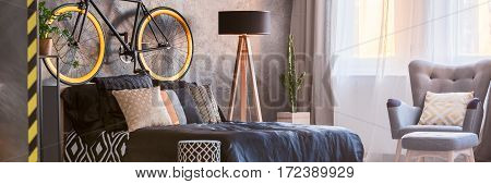 Bed, Armchair And Bicycle In Bedroom