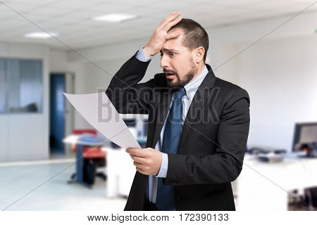 Desperate man reading a document in his office