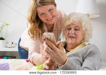Granddaughter teaching grandma how to use smart phone