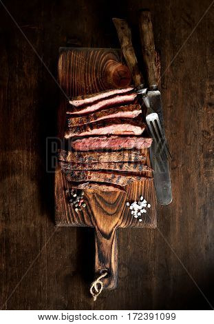 grilled beef on a board on a wooden background, knife, fork and salt