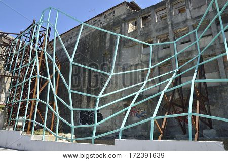 PORTO, PORTUGAL - AUGUST 5, 2015: Metamorfose green metal mesh on ruins of a building in the area around San Benito train station in Porto Portugal
