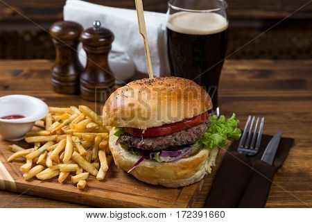 Hot Burger Serving On Wooden Board With Dark Beer