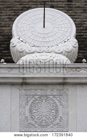 An ancient stone sundial located within the south gate area of the Xian city wall located in Shaanxi province China with traditional chinese characters representing time.