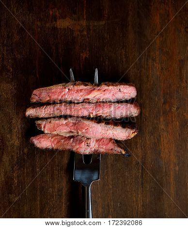 Slices of Medium rare grilled Steak Ribeye on meat fork on dark wooden background