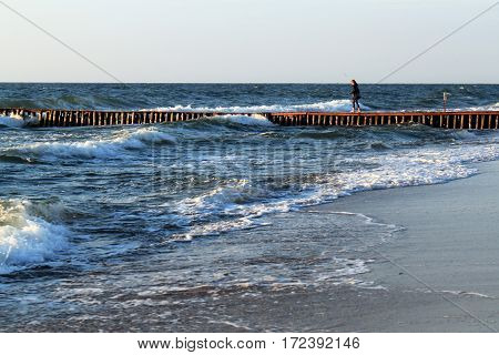 An unknown young woman walking along the old german breakwater toward to the Baltic Sea.