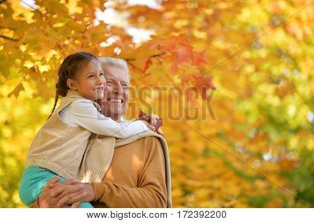 portrait of happy grandfather and granddaughter posing outdoors in autumn