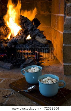 Two delicous mugs of hot chocolate by a fireplace.
