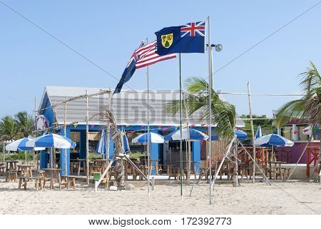 The flag of Turks & Caicos next to the wooden restaurant on Grand Turk island beach.