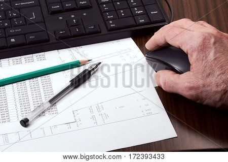 Keyboard mouse in man's hand papers pen and pencil on the table