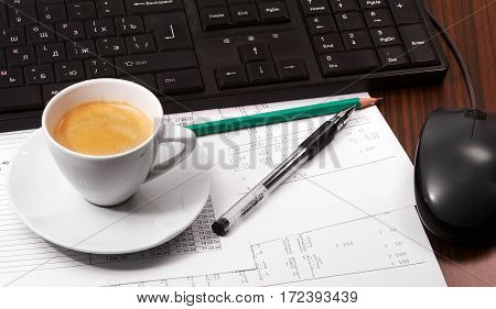Keyboard mouse papers pen pencil and cup of coffee on the table