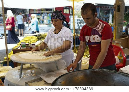 KEMER/ TURKEY - AUGUST 24, 2015: Woman and man bake Turkish bread. Kemer, Turkey