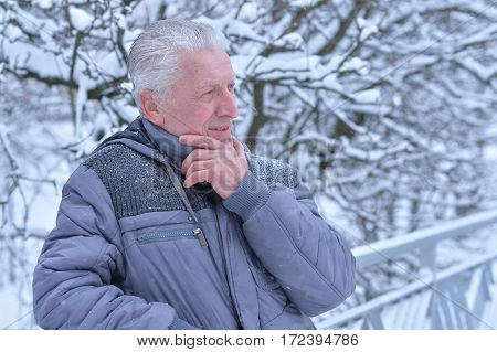Senior man so sad and thoughtfully spends time in snowy winter