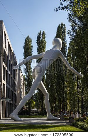 MUNICH, GERMANY - AUGUST 02, 2015: The Walking Man is a 17 meter standing sculpture designed by Jonathan Borofsky the sculpture is located on the Leopoldstraße in Munich next to the Munich Re business premises