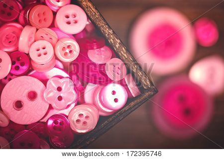 A close up of a box of pink and white buttons, with a nostalgic matte finish