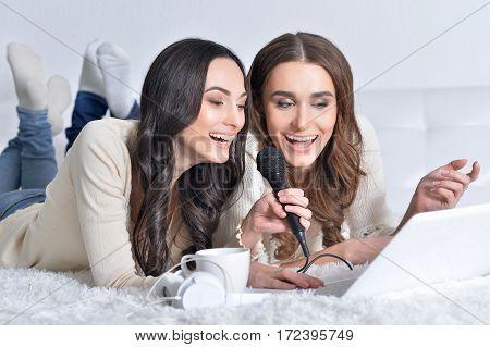 Portrait of a two young women singing karaoke