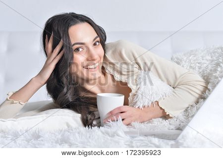 young brunette woman relaxing in bed, using laptop