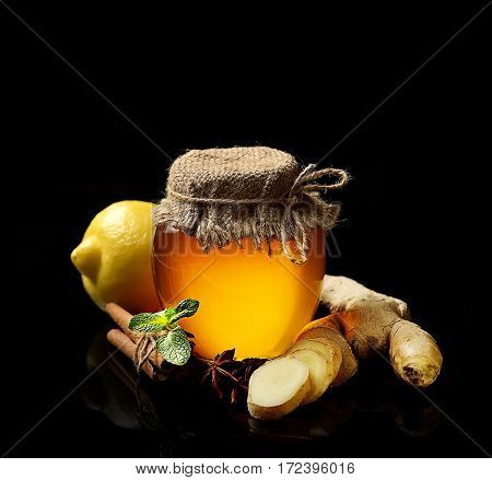 Honey, ginger, lemon and spices on a black  background