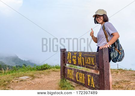 Tourist teen girl hiker wear cap and glasses with backpack smiling thumb up near nameplate attractions of Phu Chi Fa Forest Park on mountain and mist background Chiang Rai Thailand
