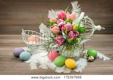 Tulip flowers and Easter eggs. Holidays decoration with birdcage. Vintage style toned picture