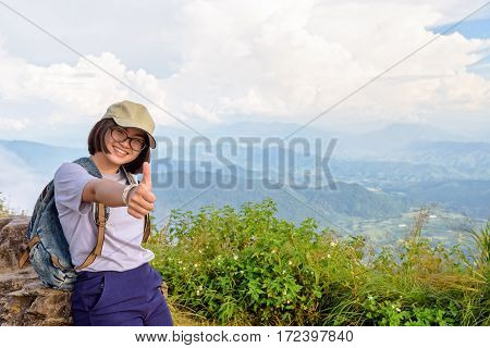 Tourist teens girl hiker wear cap and glasses with backpack poses thumb up smiling happily on high mountain at scenic point of Phu Chi Fa Forest Park in Chiang Rai Province Thailand