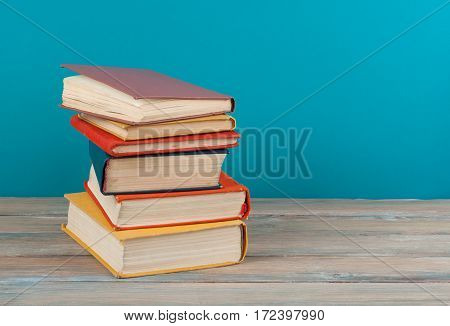 Book stacking. Open hardback books on wooden table and beige background. Back to school. Copy space for ad text