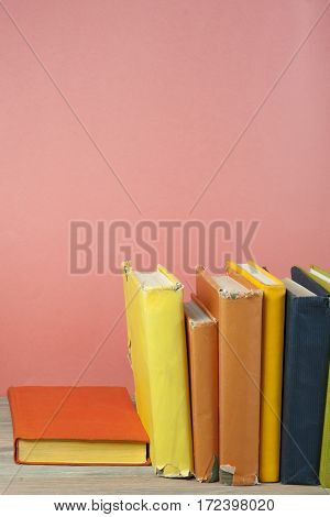 Book stacking. Open hardback books on wooden table and blue background. Back to school. Copy space for ad text.