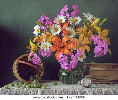 summer bouquet of lilies daisies and Phlox in the jar and gooseberries on the table.
