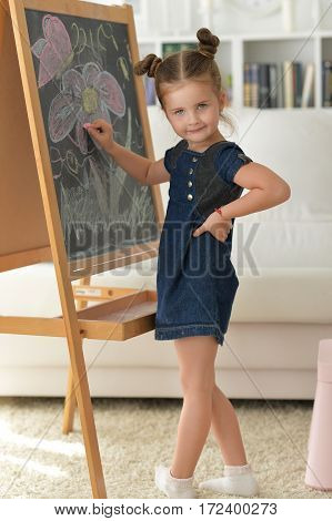 Portrait of a cute little girl drawing on chalkboard