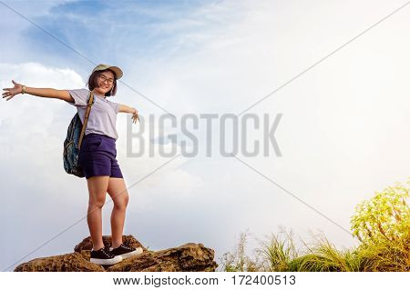 Happy hiker asian cute teens girl with backpack cap and glasses standing smiling poses open arms on mountain and sky background at Phu Chi Fa Forest Park during sunset in Chiang Rai Thailand