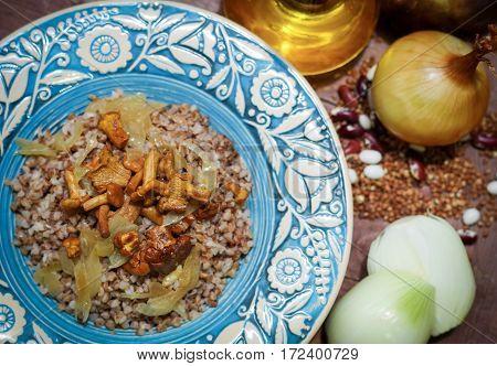 Loose gentle brown buckwheat porridge with fried chanterelles