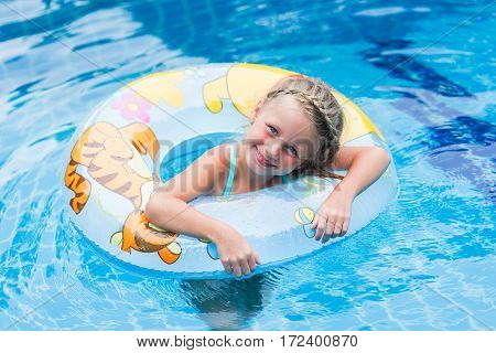 Pretty little girl swimming in outdoor pool and have a fun with inflatable circle