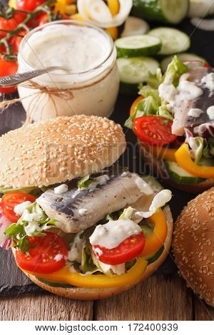 Fish Burger With Marinated Herring, Gravy And Fresh Vegetables Close-up. Vertical