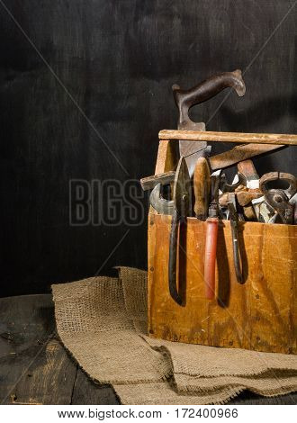 Old used tools in the toolbox. Dark background. spot lighting. Wooden box. Repair work.