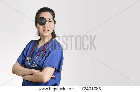 Asian female doctor wearing an eye patch looking up with arms crossed over gray background