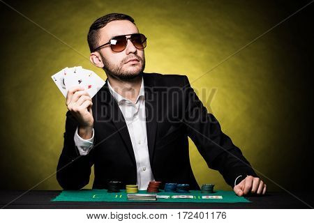 Man with four aces in hands playing on table in casino on yellow background