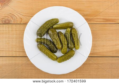 White Glass Plate With Gherkins On Wooden Table