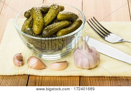 Pickled Gherkins In Transparent Bowl, Garlic, Knife And Fork On Table