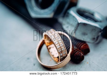 Macro Of Wedding Rings With Diamods On Grey Concrete In Day Light