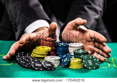 casino gambling poker people and entertainment concept - close up of poker player with chips at green casino table