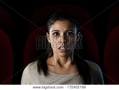 portrait young attractive Latin woman intense watching thriller or suspense drama movie alone at cinema hall theater scared sad and in shock in dark light