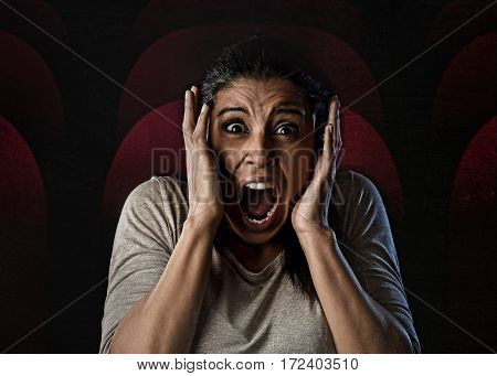 portrait young attractive Latin woman desperate and scared terrorized at cinema hall watching horror movie looking horrified in panic screaming in primal fear emotion face expression