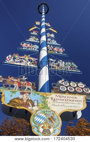 MUNICH, GERMANY - OCTOBER 31, 2015: Maypole at the Viktualienmarkt in Munich with colored figures and the brands of the local beer