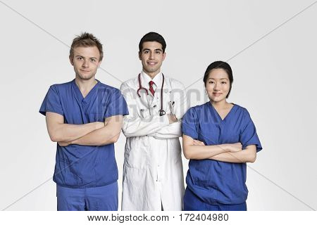 Portrait of diverse healthcare workers standing with hands folded over gray background