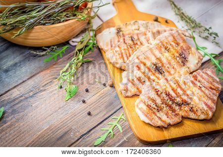 grilled beef, pork steak with herbs and spices on a rustic wooden table. Meat piece, copy space. Selective focus