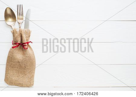 Rustic cutlery set: vintage knife fork and spoon on a white wooden background. Table with antique cutlery on the burlap with copy space top view flat lay. Cutlery wrapped in burlap.