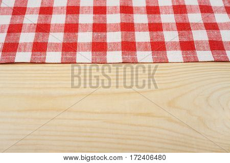Red and white tablecloth on white wooden table. Selective focus, copy space.