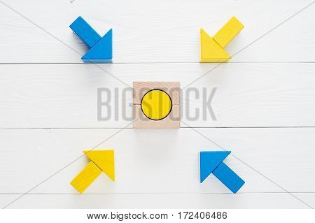 Four wooden arrows converge towards the center target with copy space top view flat lay. Arrows pointing to the object. The concept of the goal the implementation of the planned success business.