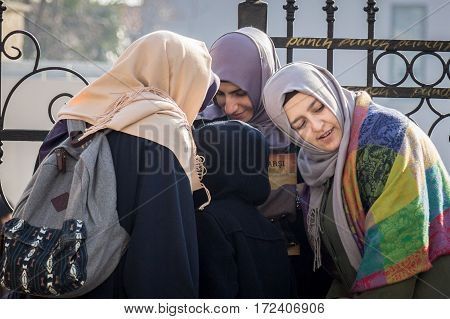 ISTANBUL TURKEY - DECEMBER 27 2015: Turkish young women wearing islamic headscarf listenning to a smartphone in group